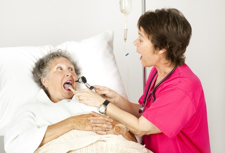 depressor: Hospital nurse uses and otoscope and tongue depressor to examine a patient.