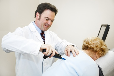 relieve: Chiropractor using a professional electronic adjustment system to relieve a patients back pain.   Stock Photo