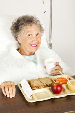 hospice: Senior woman in the hospital, eating her lunch from a tray.   Stock Photo