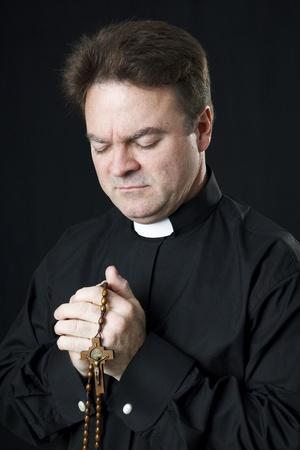 religion catolica: Sacerdote cat�lico rezando con su Rosario.   Foto de archivo