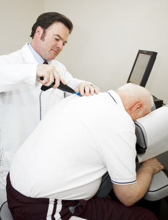 Chiropractor using a modern, electronic tool to adjust and elderly patients back.   photo