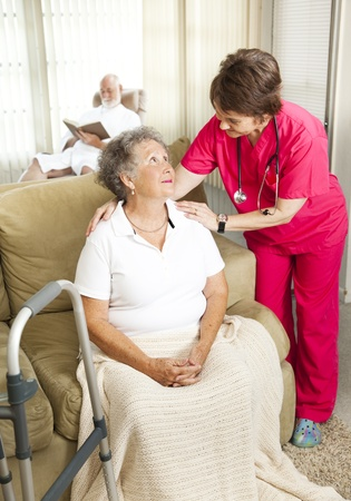 hospice: Nurse cares for an elderly woman in a nursing home.