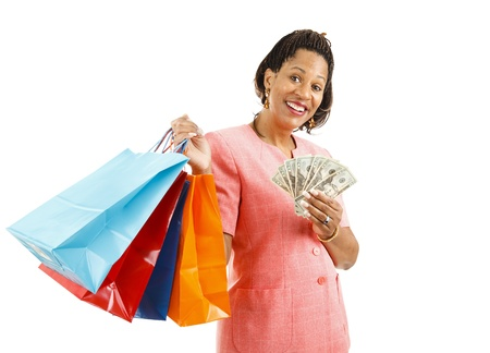 Beautiful African-american woman holding shopping bags and money.  Isolated on white.   photo