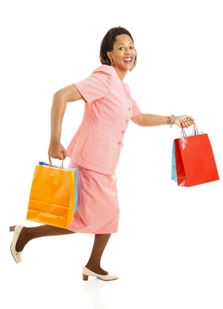 African-american female shopper running from one store to another for bargains.  Isolated on white.  photo