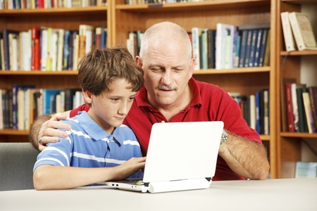 Teacher helping a student use a netbook computer in the school library. Stock Photo - 8728079