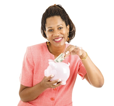 Beautiful African-american business woman saving money in a piggy bank.  Isolated on white.   photo