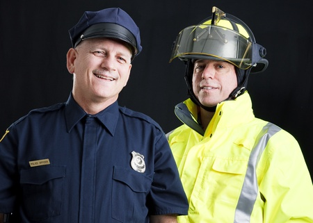 Policeman and fireman both photographed against a black background.   photo
