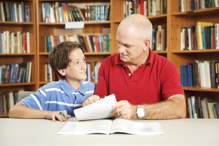 Father or male teacher tutoring a young student in the school library.   Stock Photo - 8728084