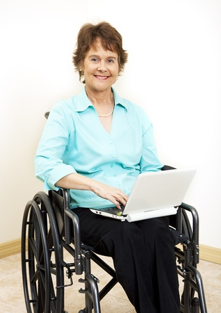 Disabled woman in wheelchair, typing on netbook computer.   photo