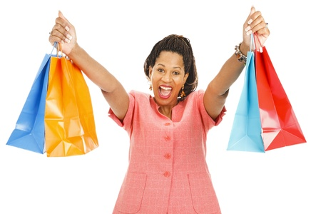 Enthusiastic african-american woman holding up her shopping bags.  Isolated on white.   photo