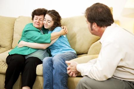 psicologia infantil: Madre e hija abrazando durante una familia en el per�odo de sesiones de asesoramiento con un terapeuta.