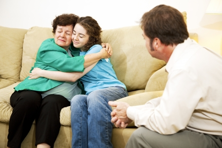 family sofa: Mother and daughter hugging during a family counseling session with a therapist.