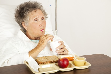 vegetable tray: Senior woman in the hospital, eating lunch and drinking from a straw.