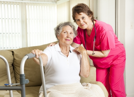 Friendly nurse cares for an elderly woman in a nursing home.   Stock Photo