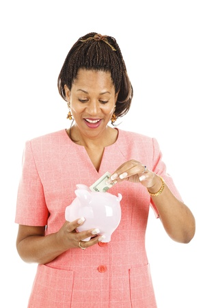 Pretty african-american woman saving money in her piggy bank.  Isolated on white.   photo
