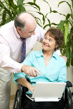Secretary in wheelchair, typing on her laptop computer while her boss looks on.   photo