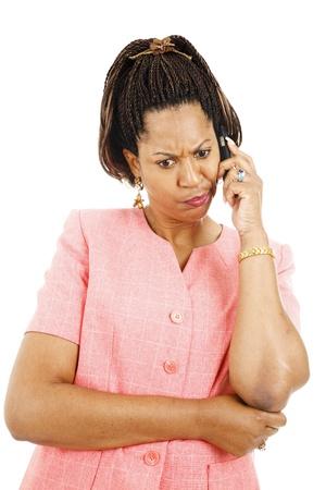 cornrows: Mujer irritada escuchando a un extra�o mensaje en su celular.  Aislados en blanco.