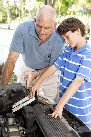 Boy helping his father change the air filter on the car engine.   photo