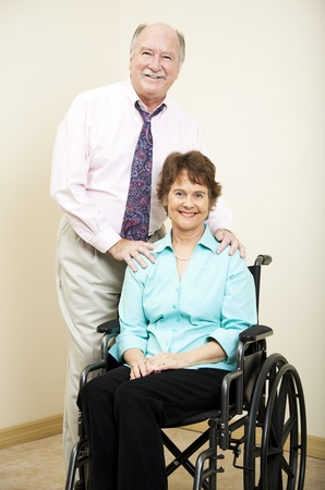 Businesswoman in a wheelchair and businessman standing beside her.   photo