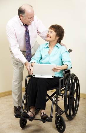 Businessman and disabled businesswoman.  She is using a laptop computer.   photo