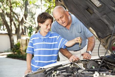 Father and son working on the car together.  The son is checking the oil.