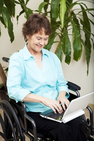 netbook: Disabled businesswoman using a tiny netbook computer.  Stock Photo