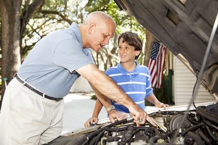 dirty car: Father teaching his young son how to repair the car.