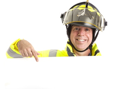 sheild: Friendly fireman in uniform, pointing to blank white space, ready for your message.