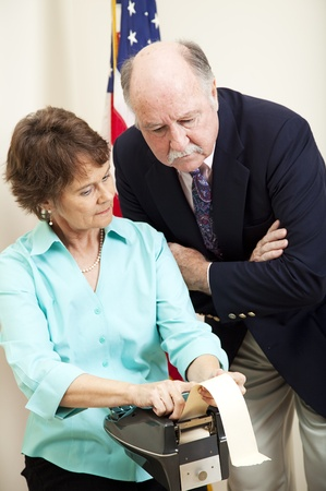 Stenographer and attorney reviewing the court transcript from her stenography machine.   photo