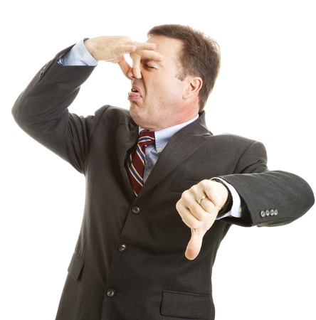 Mature businessman holds his nose and gives a thumbs-down. Isolated on white.