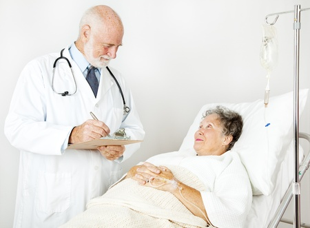 patient on bed: Doctor reviews his hospital patients medical history, taking notes.