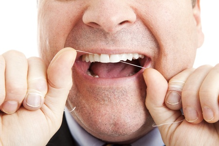 flossing: Closeup of a man flossing his teeth with dental floss.   Stock Photo