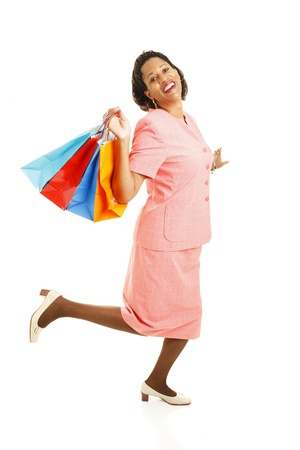 Happy african-american woman skipping along with her shoppping bags.  Full body isolated on white.   photo