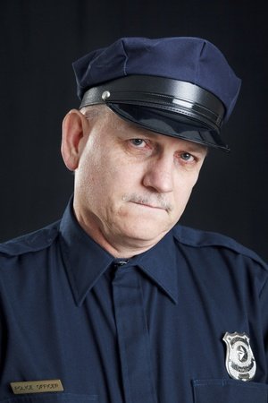 Sad police officer with a tear rolling down his face.  Black background. Stock Photo - 9017519
