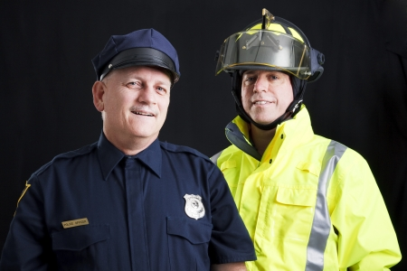 Public employees, a firefighter and a police officer, smiling and happy.  Black background. photo