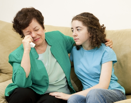 child crying: Teenage girl tries to comfort her crying mother.