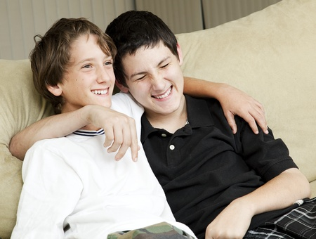 brothers: Two young brothers laughing together at home.