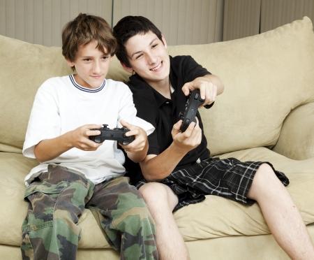 ni�os jugando videojuegos: Dos hermanos en casa jugando videojuegos juntos.   Foto de archivo