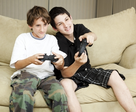 Two brothers at home playing video games together.   photo