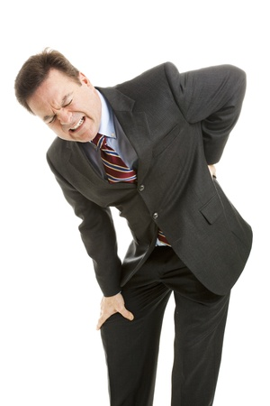 short back: Mature businessman doubled over with back pain.  Isolated on white.