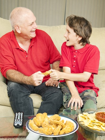 Father and son playfully fighting over a chicken wing as they watch the football game. Stock Photo - 9077771