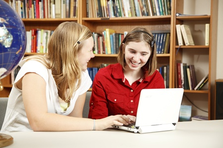 netbook: Teen girls using the computer in the school library.