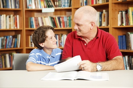 Tutor or father helping a boy with his homework in the library.   photo