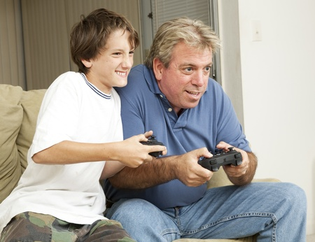 Father or uncle playing video games with a little boy - his son or nephew.   photo