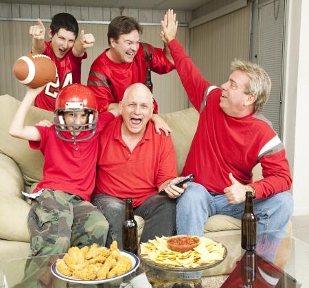 personas viendo television: Hinchas entusiasmados porque su equipo est� ganando.   Foto de archivo