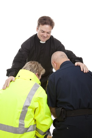 Priest or pastor gives blessing to a firefighter and a police officer who are kneeling in prayer.  White background.   photo