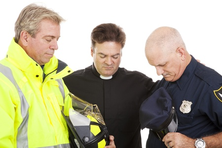 Priest of minister leads a firefighter and a policeman in prayer.  White background.   photo