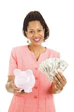 Beautiful african-american woman saving money in her piggy bank.  Isolated on white.   photo