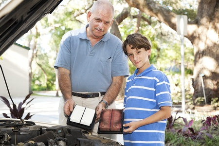 Father and son changing the air filter in the family car.   photo