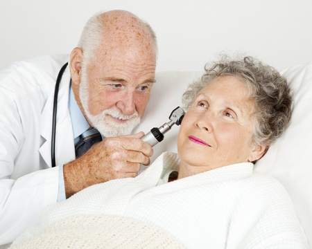 otoscope: Doctor using an otoscope to examine a hospital patients ear canal.